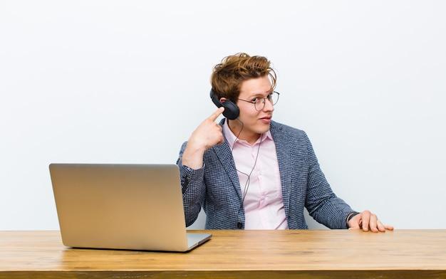 Jeune homme d'affaires à tête rouge travaillant dans son bureau avec un casque