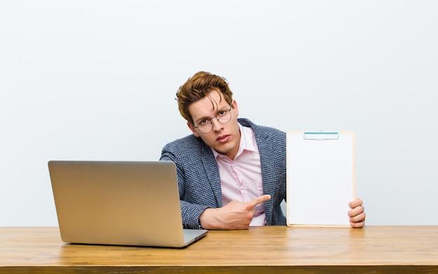 Jeune homme d'affaires à la tête rouge travaillant dans son bureau avec une feuille de papier