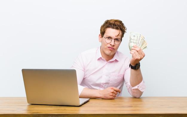 Jeune homme d'affaires à tête rouge travaillant à son bureau, concept d'argent