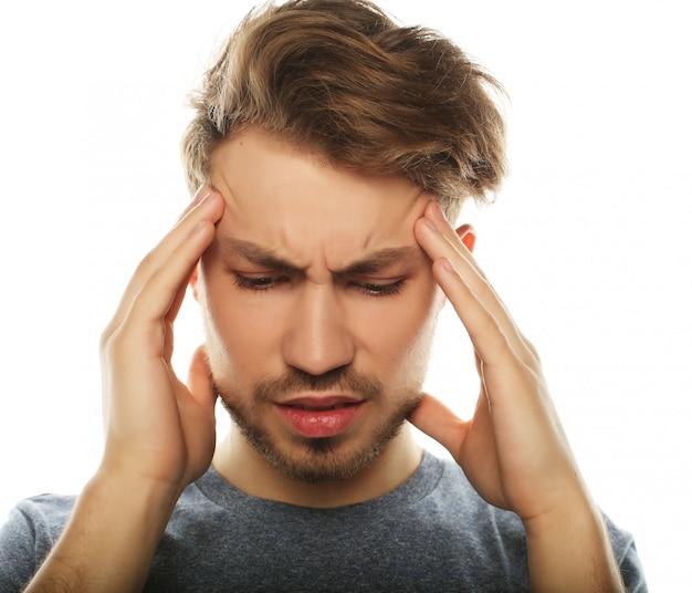 Jeune homme d'affaires touchant sa tête et gardant les yeux fermés