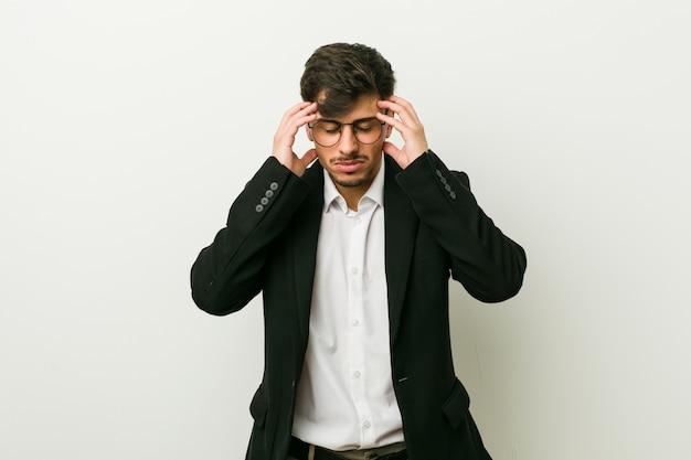 Jeune homme d'affaires touchant les temples et ayant des maux de tête
