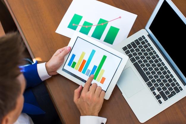 Jeune homme d'affaires travaillant avec des appareils modernes, ordinateur tablette numérique et téléphone portable
