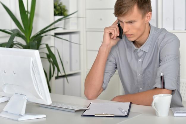 Jeune homme d'affaires travaillant au bureau au bureau avec ordinateur et téléphone