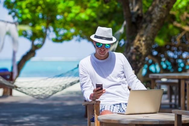 Jeune homme d'affaires travaillant dans un café en plein air