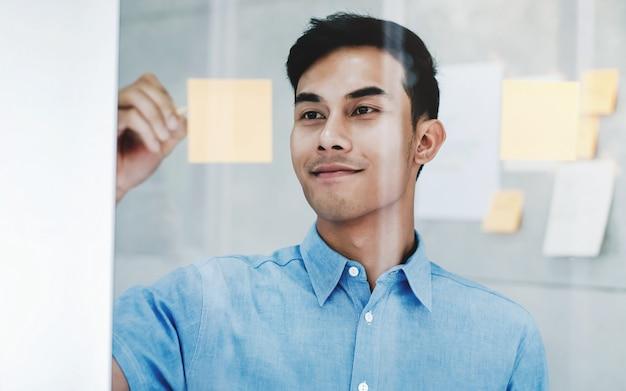 Jeune homme d'affaires travaillant dans la salle de réunion de bureau. planification et projet de données