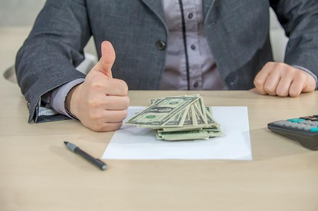 Jeune homme d'affaires travaillant depuis son bureau et comptant l'argent comptant
