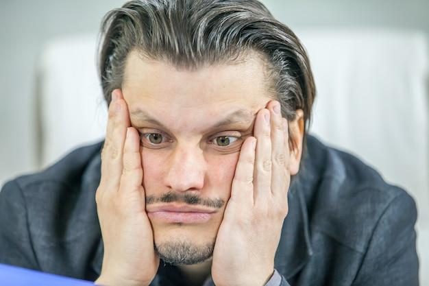 Jeune homme d'affaires travaillant depuis son bureau - le concept de l'échec