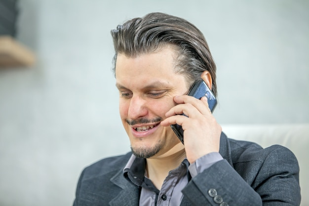 Jeune homme d'affaires travaillant depuis son bureau tout en parlant au téléphone