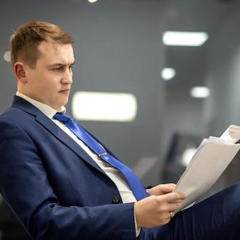 Jeune homme d'affaires travaillant avec des documents en parcourant des papiers dans un dossier, assis au bureau.