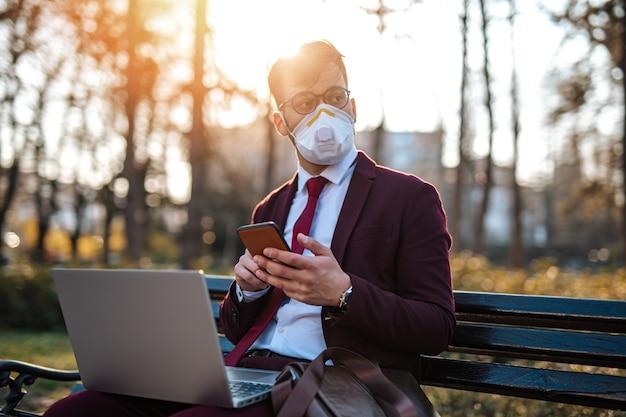 Jeune homme d'affaires travaillant sur un ordinateur portable assis sur un banc, portant un masque de protection et utilisant un téléphone intelligent.