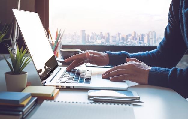 Jeune homme d'affaires travaillant sur ordinateur portable au bureau avec vue sur la ville de fenêtre