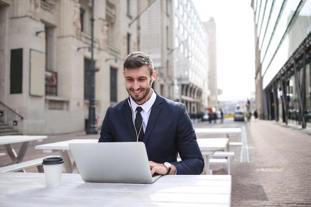 Jeune homme d'affaires travaillant en plein air