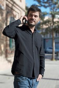 Jeune homme d'affaires urbain sur smartphone dans la rue parler sur smartphone