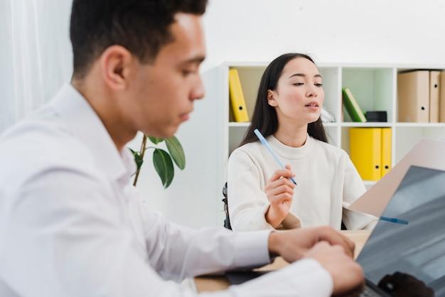 Jeune homme d'affaires utilisant un ordinateur portable et son collègue lisant le document au bureau