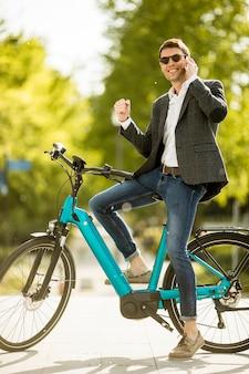 Jeune homme d'affaires sur le vélo électrique à l'aide de téléphone mobile