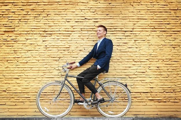 Jeune homme d'affaires à vélo sur fond de mur de brique jaune