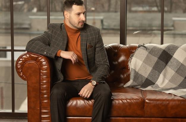 Jeune homme d'affaires vérifiant l'heure sur sa montre et assis sur un canapé