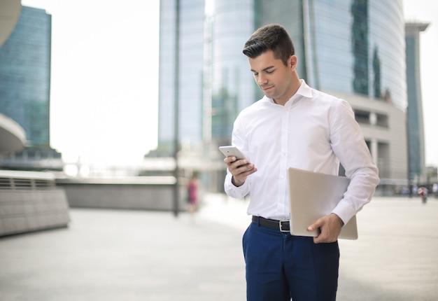 Jeune homme d'affaires vérifiant son smartphone en se réveillant dans la rue