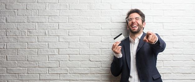 Jeune homme d'affaires vêtu d'un costume contre un mur de briques blanches criant