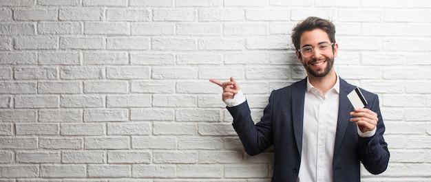 Jeune homme d'affaires vêtu d'un costume contre un mur de briques blanches pointant vers le côté