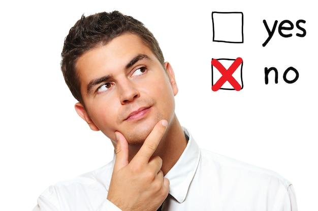 Un jeune homme d'affaires votant pour non sur fond blanc