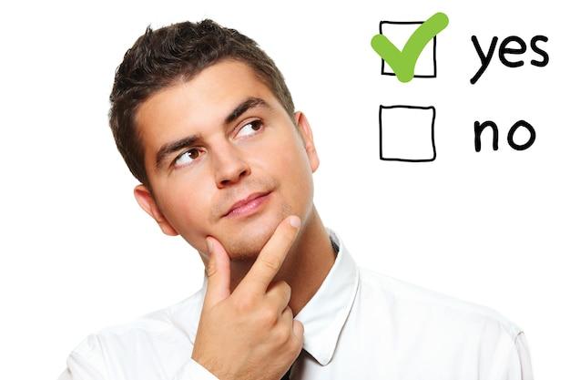 Un jeune homme d'affaires votant pour oui sur fond blanc