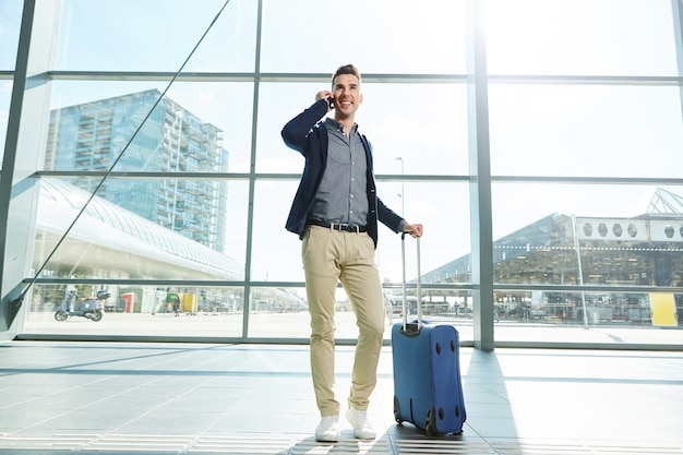 Jeune homme d'affaires voyageant à l'aéroport appelant au téléphone