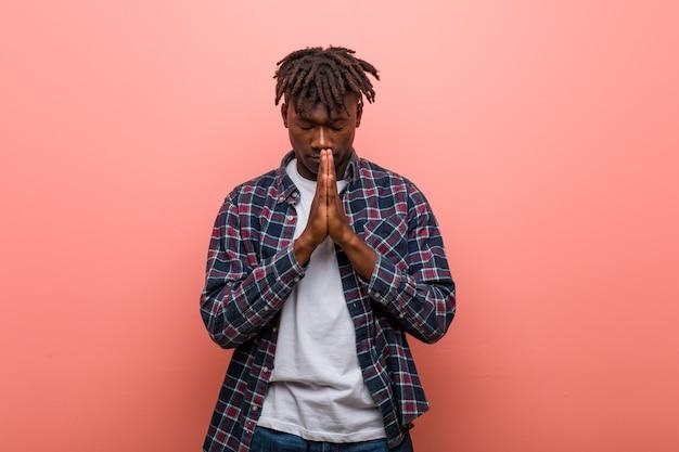 Jeune homme africain africain tenant les mains dans la prière près de la bouche, se sent confiant.