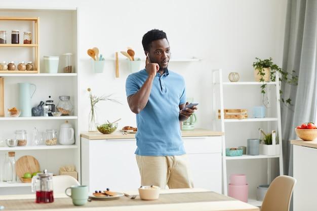 Jeune homme africain à l'aide d'écouteurs pour parler au téléphone mobile en se tenant debout dans la cuisine à la maison