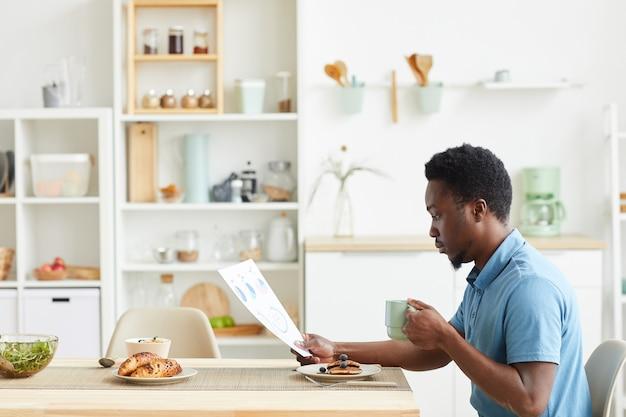 Jeune homme africain assis à la table dans la cuisine, il prend le petit déjeuner et la lecture du contrat commercial