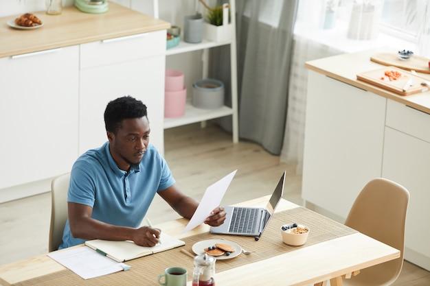 Jeune homme africain assis à la table devant un ordinateur portable et travaillant avec des documents dans la cuisine