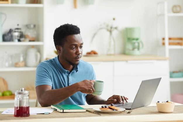 Jeune homme africain assis à la table, il prend le petit déjeuner et à l'aide d'un ordinateur portable dans la cuisine à la maison