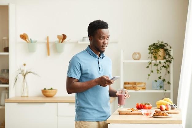 Jeune homme africain buvant un cocktail frais et utilisant son téléphone portable en se tenant debout dans la cuisine