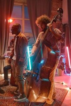 Jeune homme africain chantant pendant que ses collègues jouent des instruments de musique sur scène en boîte de nuit