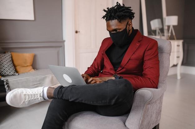Un jeune homme africain confiant regarde la vidéoconférence de la webcam au bureau