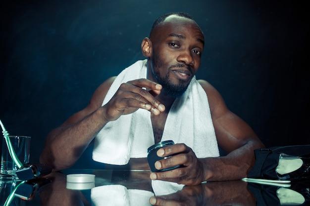 Le jeune homme africain dans la chambre assis devant le miroir après s'être gratté la barbe à la maison. concept d'émotions humaines. concepts de crème après-rasage