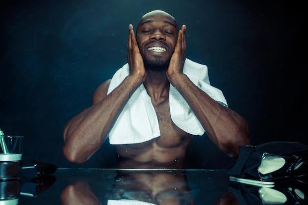 Le jeune homme africain dans la chambre assis devant le miroir après s'être gratté la barbe à la maison. concept d'émotions humaines