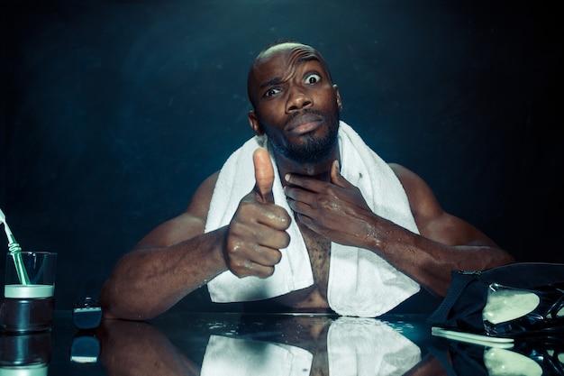 Jeune homme africain dans la chambre assis devant le miroir après s'être gratté la barbe à la maison. concept d'émotions humaines