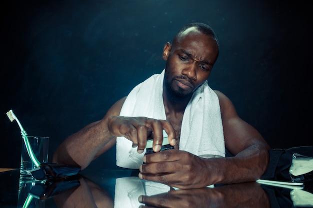 Jeune homme africain dans la chambre assis devant le miroir après s'être gratté la barbe à la maison.