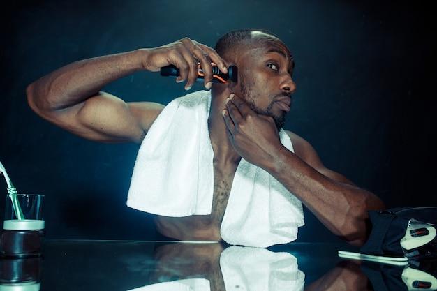 Jeune homme africain dans la chambre assis devant le miroir se gratter la barbe à la maison. concept d'émotions humaines