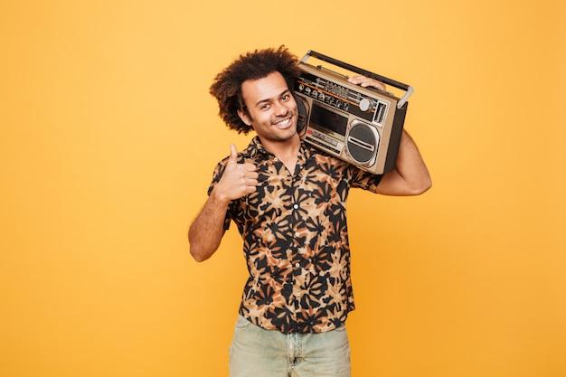 Jeune homme africain debout avec un magnétophone montrant les pouces vers le haut.