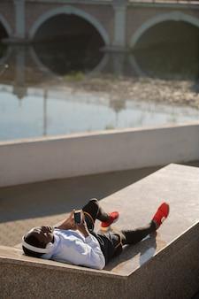 Jeune homme africain détendu en tenue de sport et casque blanc au bord de la rivière après un entraînement en plein air et profiter de repos avec de la musique