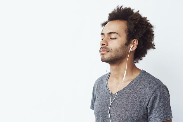 Jeune homme africain, écouter de la musique dans les écouteurs avec les yeux fermés.