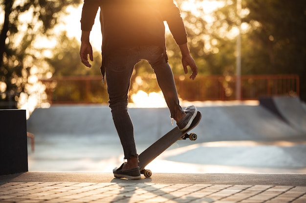 Jeune homme africain, faire du skateboard en plein air