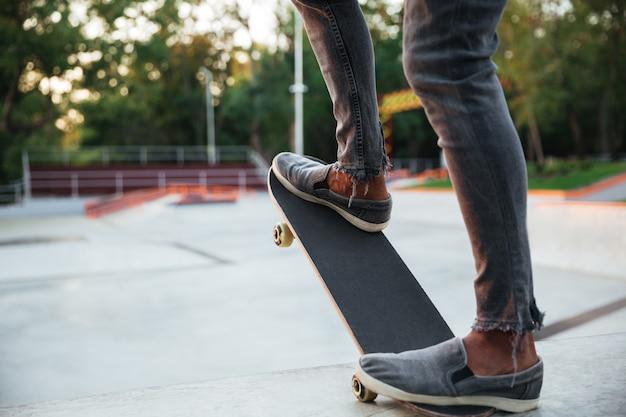 Jeune homme africain faisant du skateboard