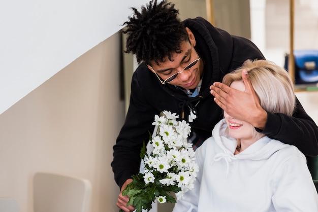 Un jeune homme africain fermant les yeux de sa petite amie tenant un bouquet de fleurs à la main