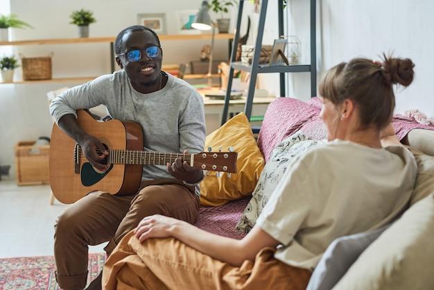 Jeune homme africain jouant de la guitare et chantant des chansons pour sa petite amie sur le canapé de la chambre