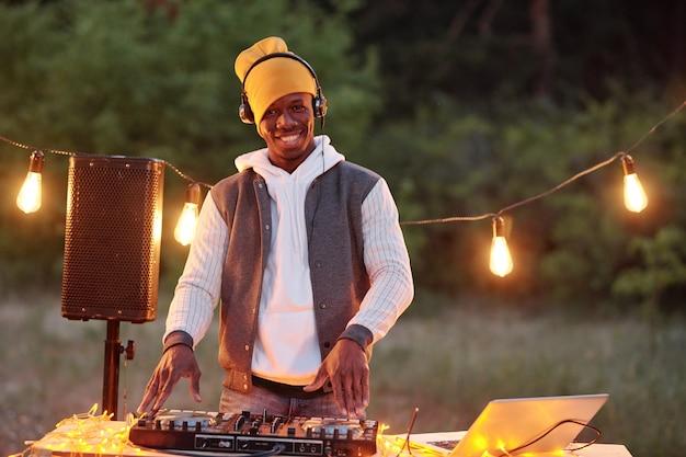 Jeune homme africain joyeux avec un casque vous regarde avec le sourire en se tenant debout par carte stéréo avec platines à l'extérieur