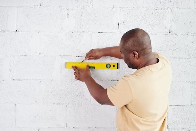 Jeune homme africain avec une ligne de dessin au crayon sur un outil à main de mesure de niveau sur un mur de briques peintes en blanc lors de la rénovation du salon