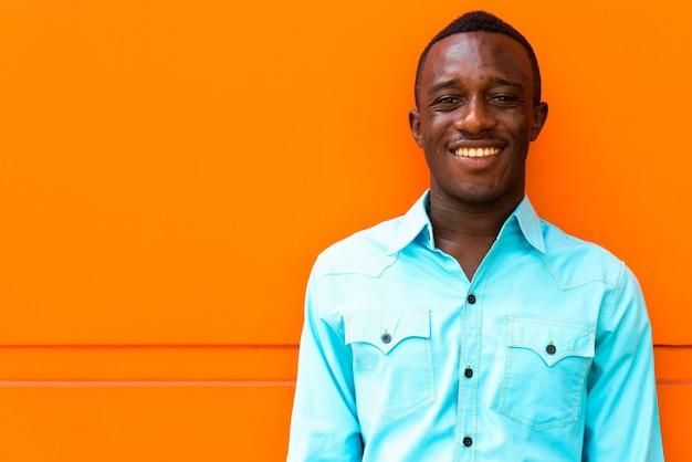 Jeune homme africain noir heureux souriant tout en s'appuyant contre le mur orange